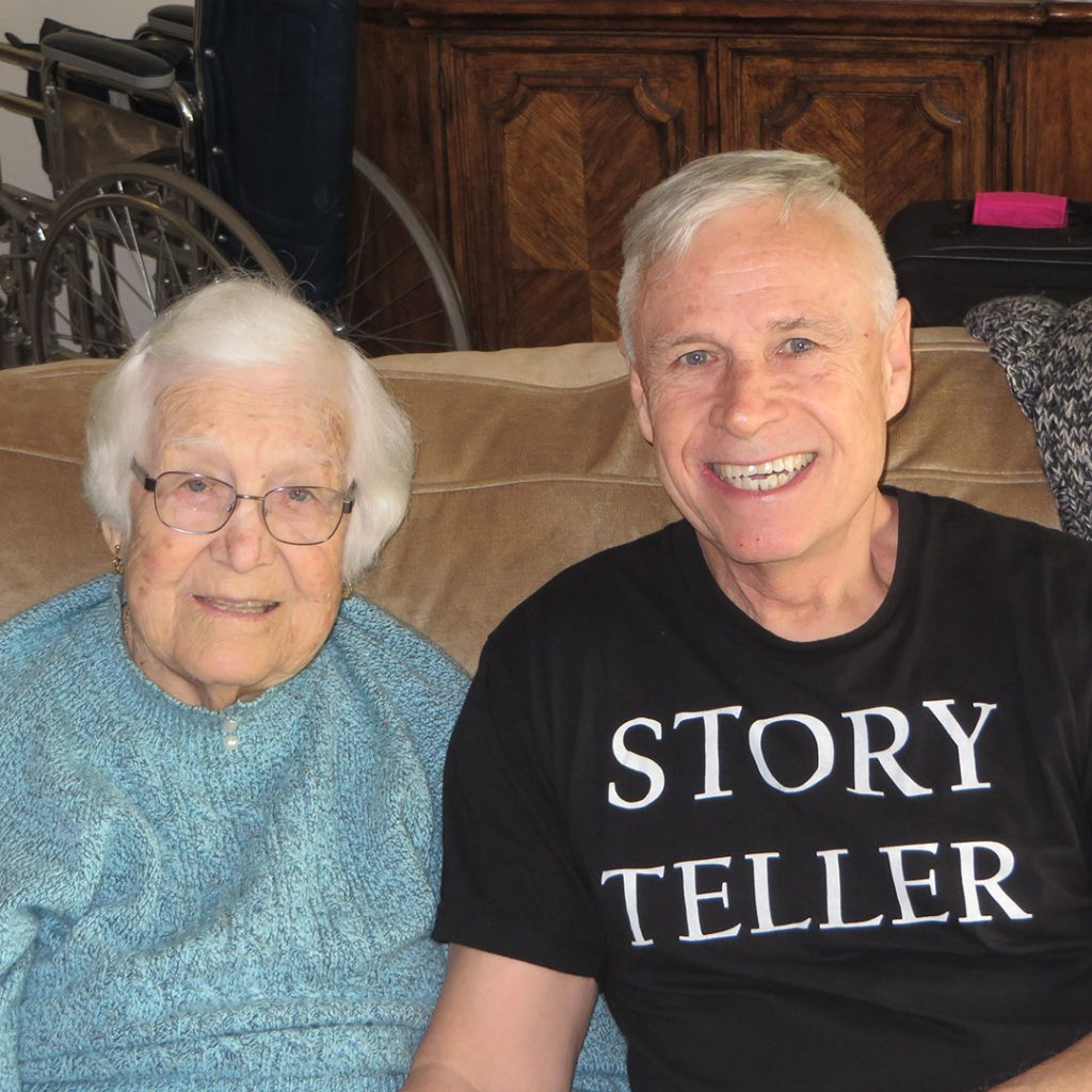 Frances and Ned Buratovich, wearing Story Teller T-shirt, seated on couch.